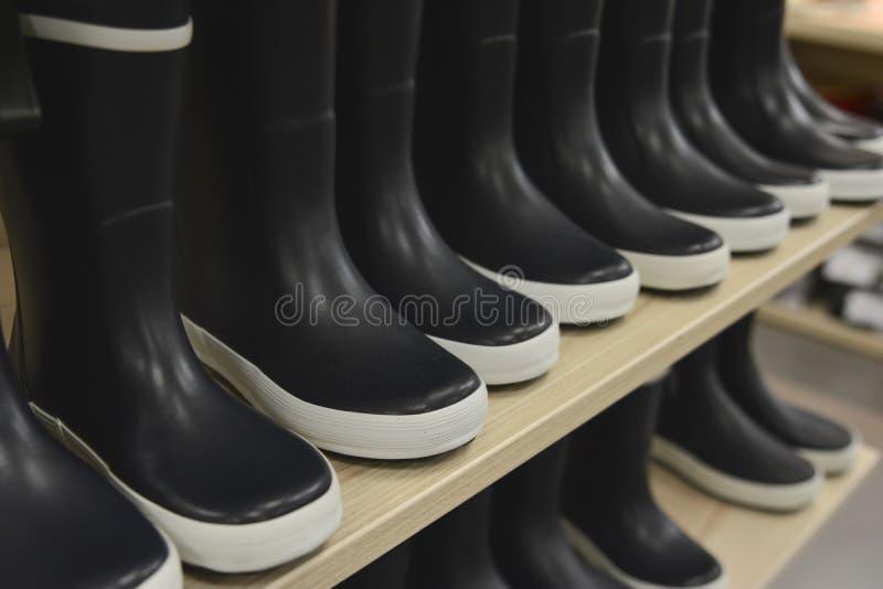 Schwarze Gummistiefel auf Ladenregalen in einem Shop lizenzfreies stockbild