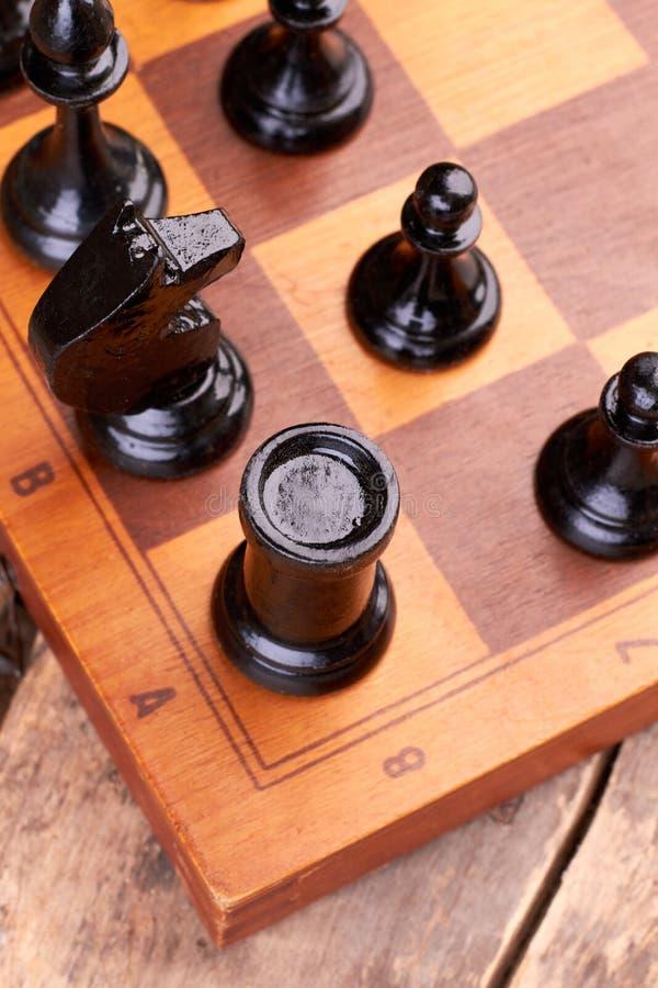Schwarze hölzerne Schachfiguren gesetzt auf Schachbrett stockbilder