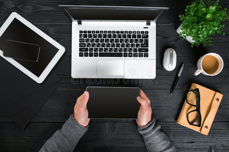 Schwarze hölzerne Tischplattendraufsicht des Hippies, männliche Hände, die auf einem Laptop schreiben lizenzfreie stockfotografie