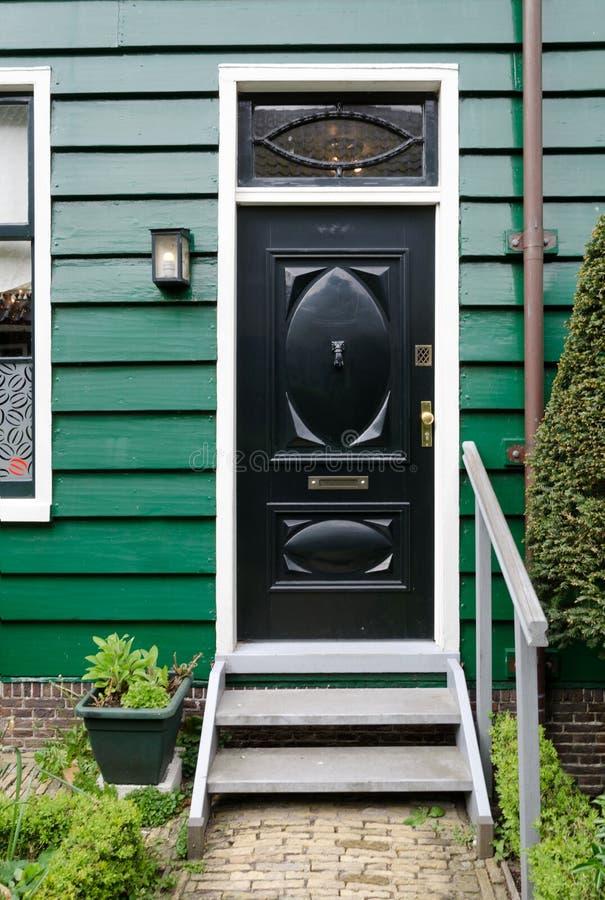 Schwarze Holztür mit grünem Wandhaus lizenzfreie stockfotos