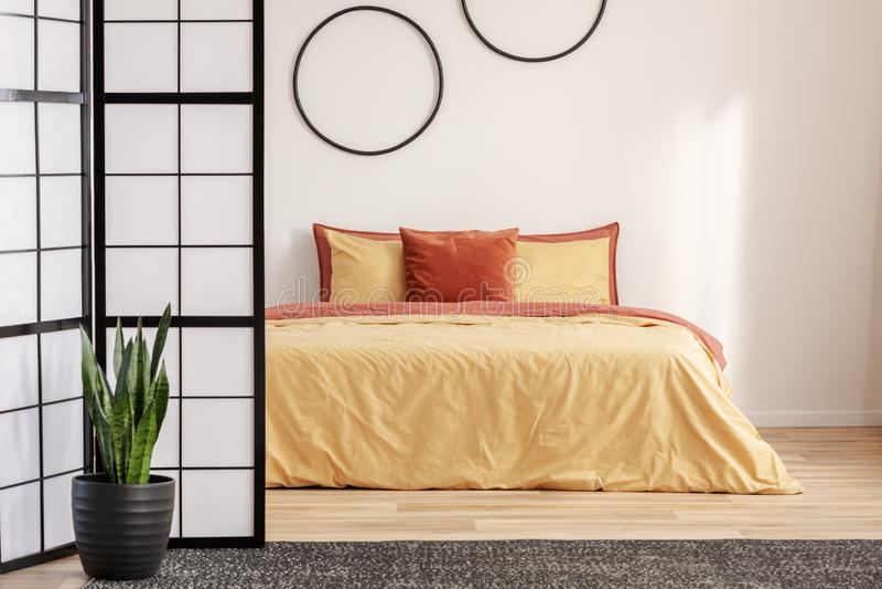 Schwarze Hopfen auf einer weißen Wand im Schlafzimmer mit orangefarbenem Bett stockfoto