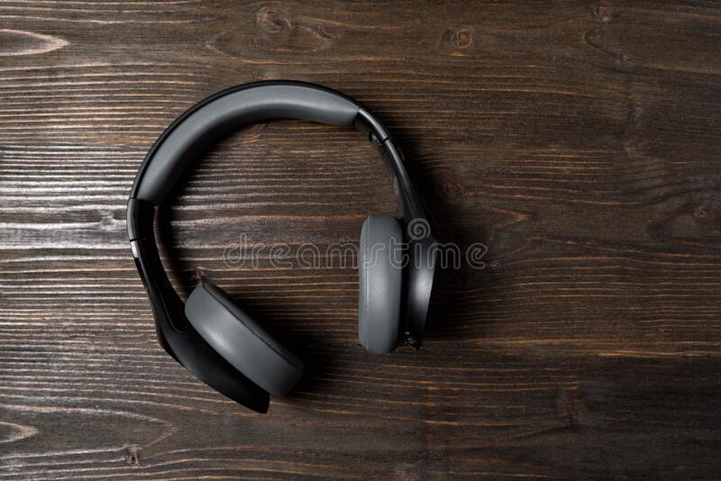 Schwarze kabellose Ohrhörer auf dunklem Holzboden Stereo-Kopfhörer Oberansicht stockfotos