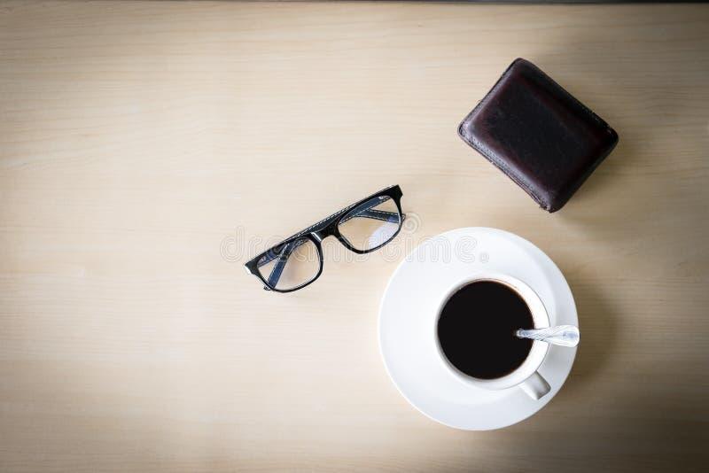 Schwarze Kaffeetasse auf dem hölzernen Hintergrund lizenzfreie stockfotos