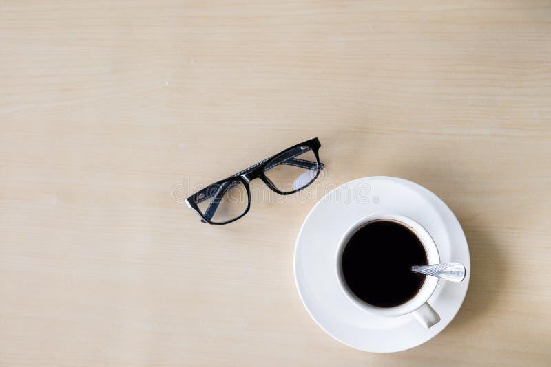 Schwarze Kaffeetasse auf dem hölzernen Hintergrund lizenzfreies stockfoto