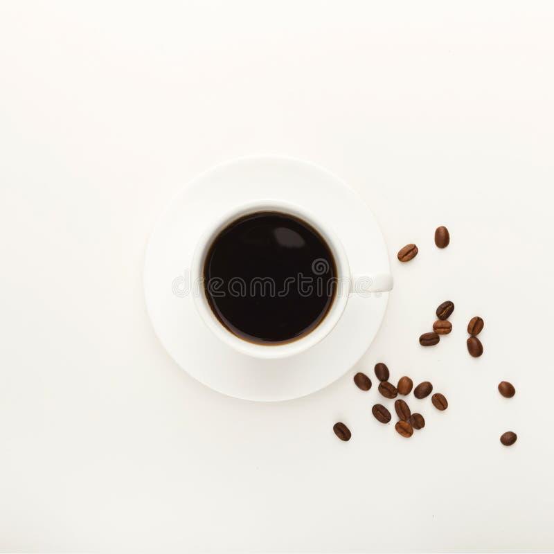 Schwarze Kaffeetasse und gebratene Bohnen lokalisiert auf Weiß stockfotografie