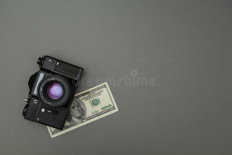 Schwarze Kamera und hundert Dollar stockfotos