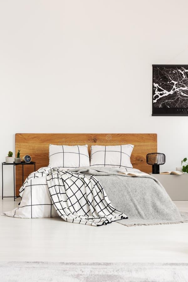 Schwarze Karte auf weißer Wand über hölzerner Kopfende im einfachen Schlafzimmerinnenraum lizenzfreie stockfotos