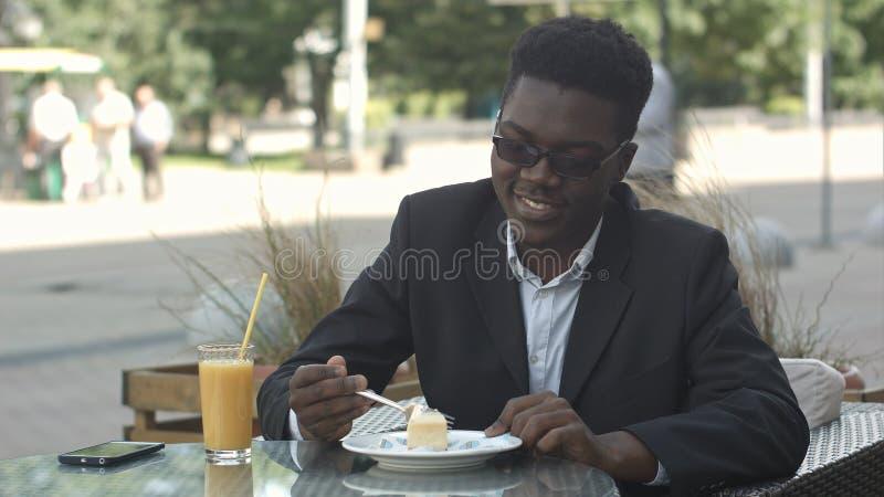 Schwarze Kellnerumhüllungsterrassen-Cafégäste bei Tisch lizenzfreie stockfotos