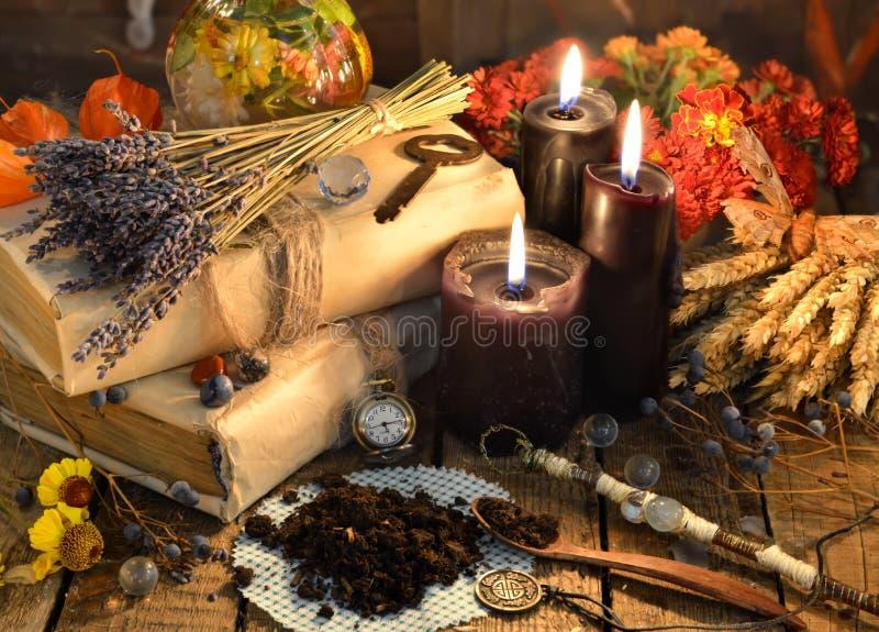 Schwarze Kerzen, alte Bücher, Lavendelblumen und magische Gegenstände auf Hexentabelle lizenzfreie stockbilder
