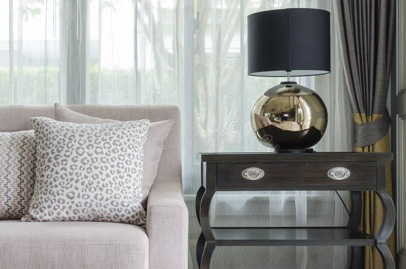 Schwarze klassische Lampe auf Holztisch im Luxuswohnzimmer stockfotografie