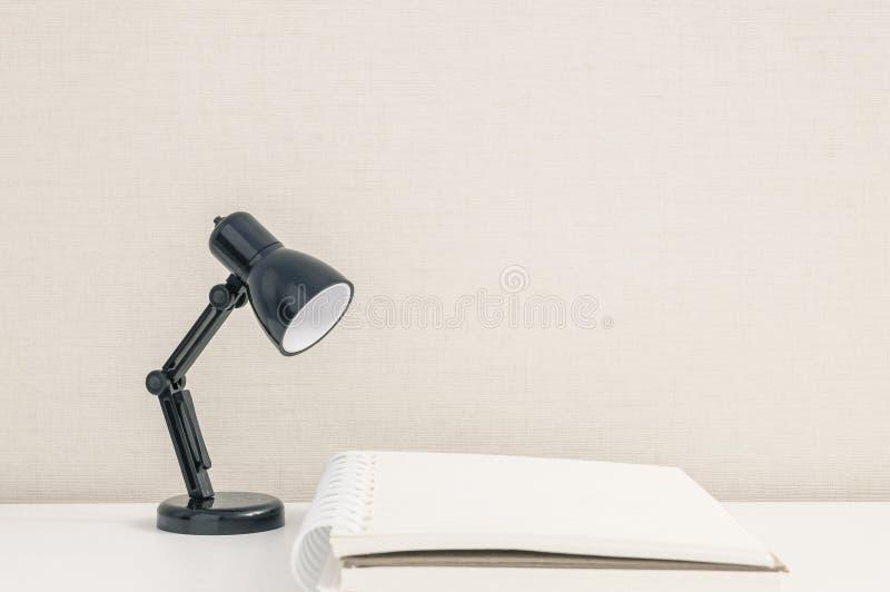 Schwarze kleine Lampe der Nahaufnahme auf unscharfer weißer hölzerner Schreibtisch- und Cremetapetenwand maserte Hintergrund mit  stockbild