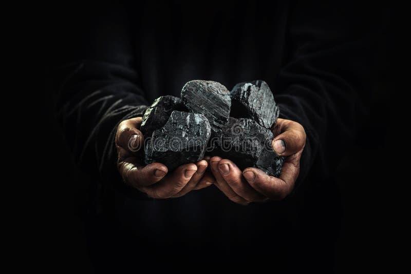 Schwarze Kohle in den Händen, Schwerindustrie, Heizung stockbilder