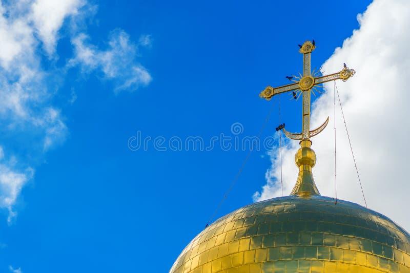 Schwarze Krähen sitzen auf dem goldenen Kreuz der orthodoxen Kirche stockfotografie