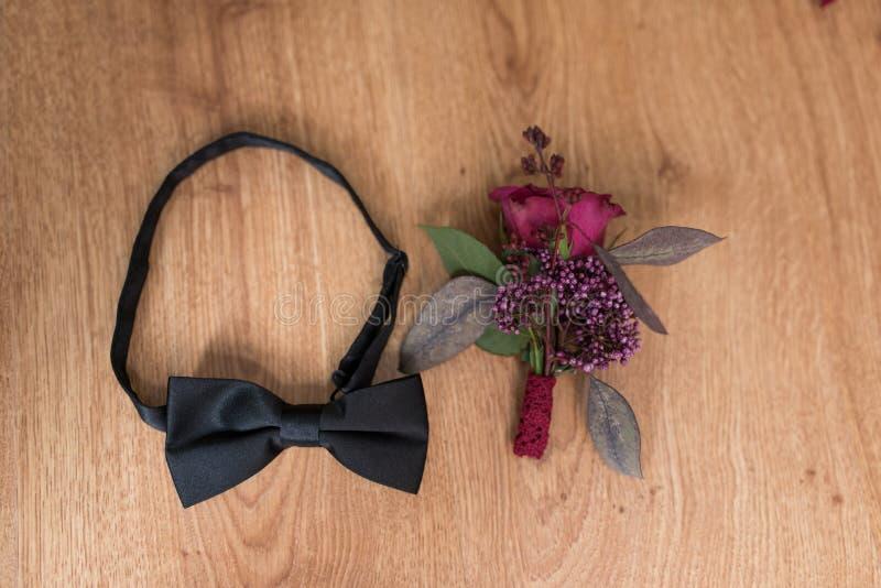 Schwarze Krawatte und ein Dekorationsknopfloch auf braunem Hintergrund Dekoration gemacht von den Rosen, Zierpflanzen stockbild