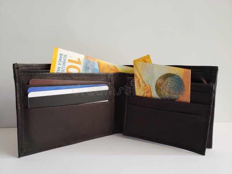 schwarze lederne Geldbörse mit SchweizerBanknoten und weißem Hintergrund lizenzfreie stockfotografie