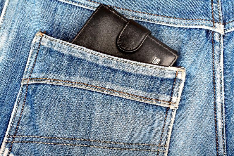 Schwarze lederne Geldbörse, die in der Gesäßtasche von Jeans haftet lizenzfreie stockfotografie