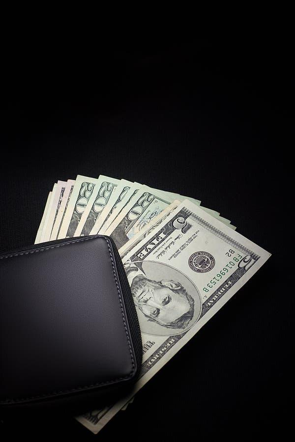 Schwarze lederne Geldbörse mit den Bargelddollar lokalisiert auf einem schwarzen backg stockfotografie