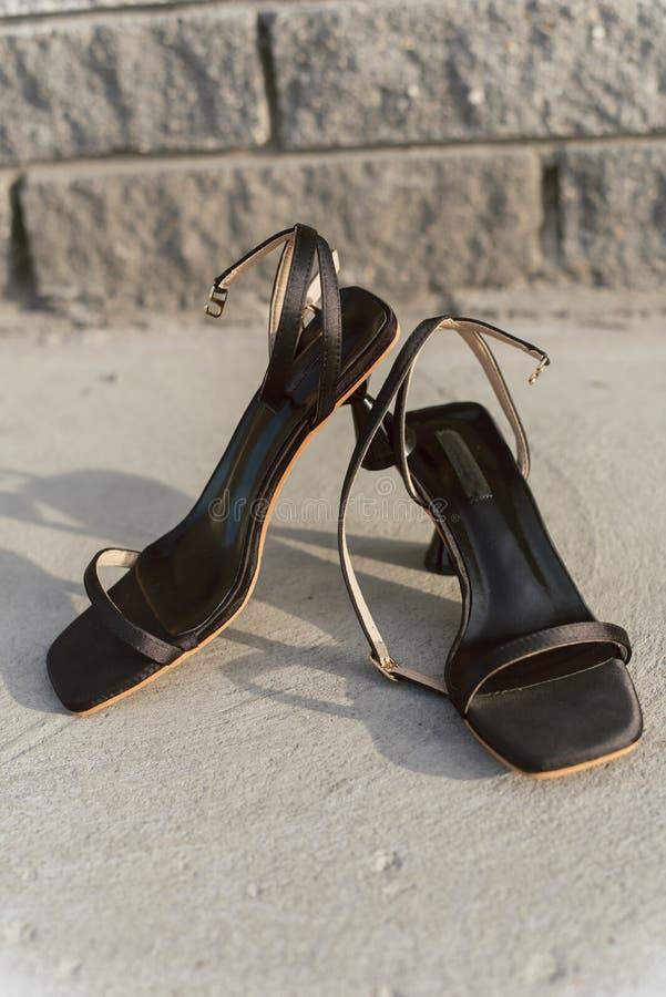 Schwarze lederne offene Sandalen mit Fersen stehen auf dem Asphalt in der Sonne Frauen `s Schuhe Vertikales Foto von stilvollem u lizenzfreie stockfotografie