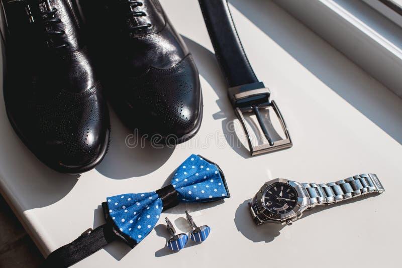 Schwarze Lederschuhe und Gurt, Uhr, blaue Fliege und Manschettenknöpfe, auf einem weißen Fensterbrett Zusatz für Gesellschaftskle stockfotografie
