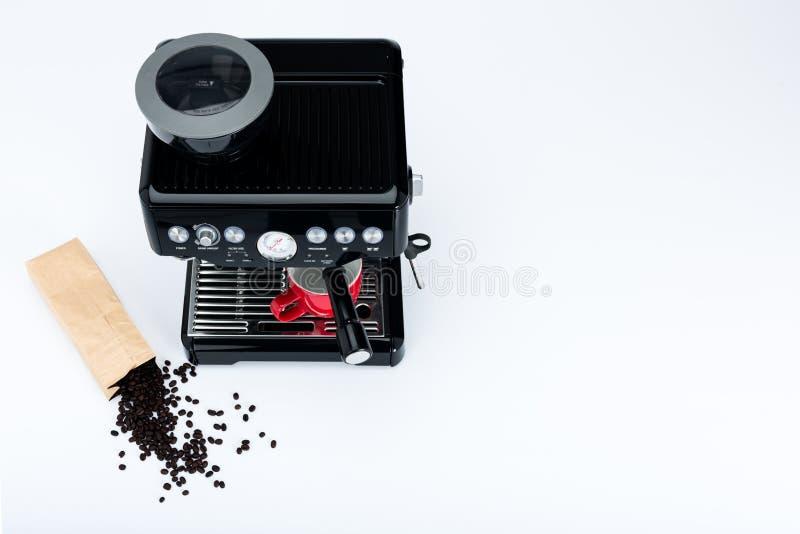 Schwarze manuelle Kaffeemaschine mit Schleifer und roter Kaffeetasse und Tasche von frisch Röstkaffeebohnen auf weißem Hintergrun lizenzfreie stockfotografie