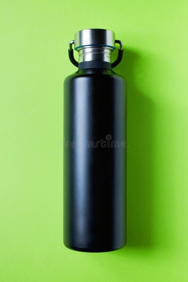 Schwarze Metallwasserflasche auf Grün stockfotos