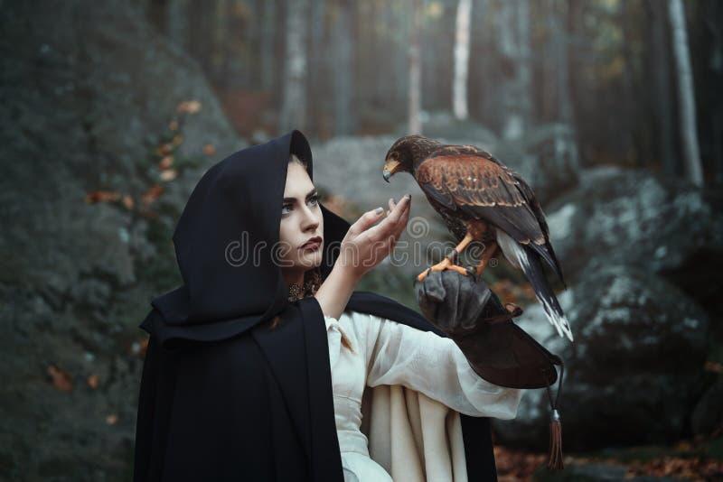 Schwarze mit Kapuze Jägerin mit Falken stockfoto