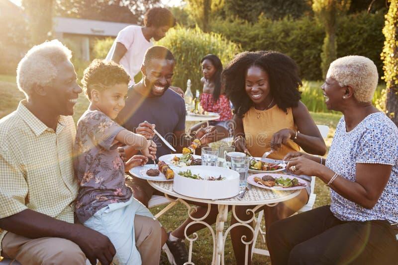 Schwarze multi Generationsfamilie, die an einem Tisch im Garten isst lizenzfreies stockfoto