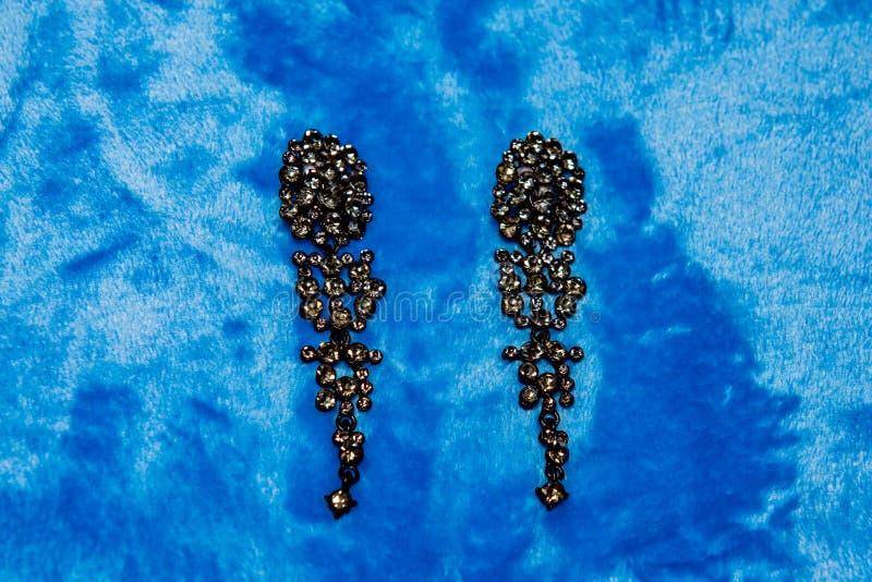 Schwarze Ohrringe auf blauem Hintergrund stockfotos