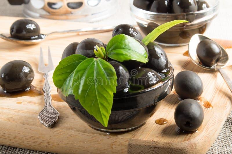 Schwarze Oliven auf einem hölzernen Behälter lizenzfreie stockfotos