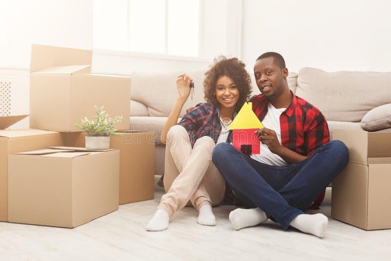 Schwarze Paare, die auf Boden an der neuen Wohnung sitzen stockfoto