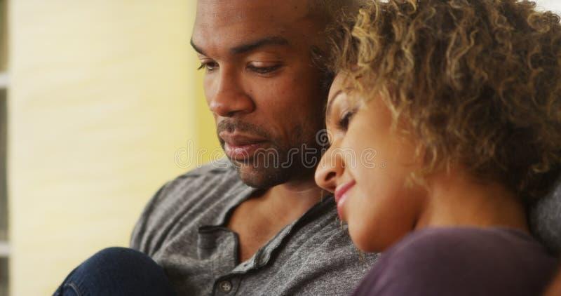 Schwarze Paare, die auf dem Couchlächeln sitzen stockbild