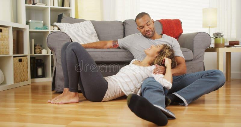 Schwarze Paare, die auf der Bodenunterhaltung sitzen stockfoto