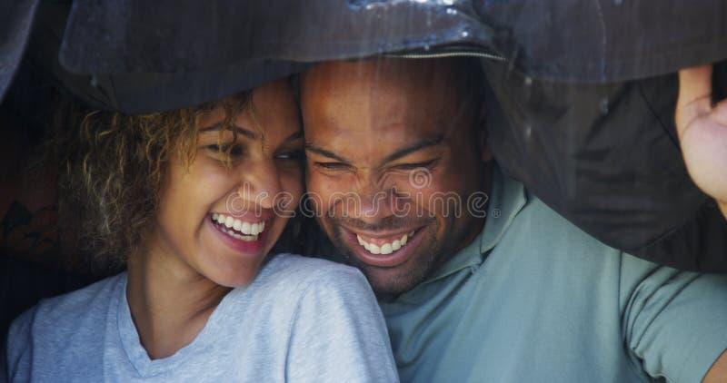 Schwarze Paare, die unter dem Mantel versucht, naß nicht zu erhalten stehen stockfoto