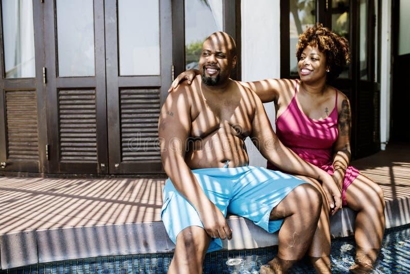 Schwarze Paare, die zusammen an Erholungsort Poolside sitzen lizenzfreies stockfoto