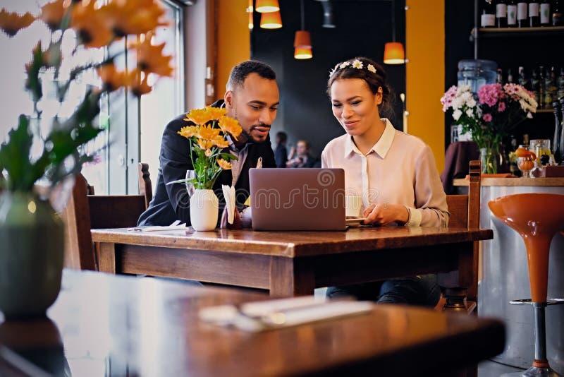 Schwarze Paare unter Verwendung des Laptops in einem Café stockfoto