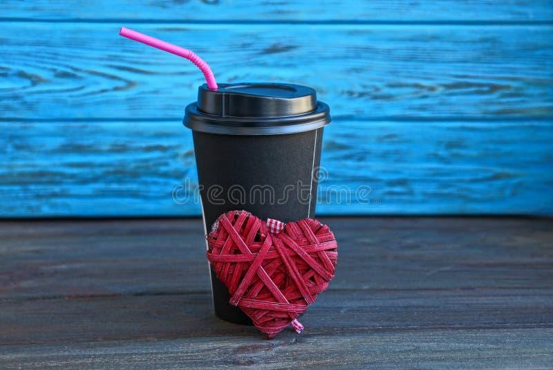 Schwarze Papierschale mit Kaffee und einem roten Herzen auf einer Tabelle nahe der blauen Wand stockfotografie