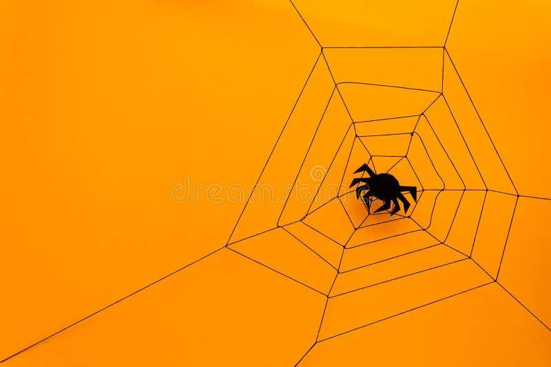 Schwarze Papierspinne mit Netz auf gelbem Hintergrund Ein grimmiger Minireaper, der eine Sense anhält, steht auf einem Kalenderta lizenzfreies stockbild