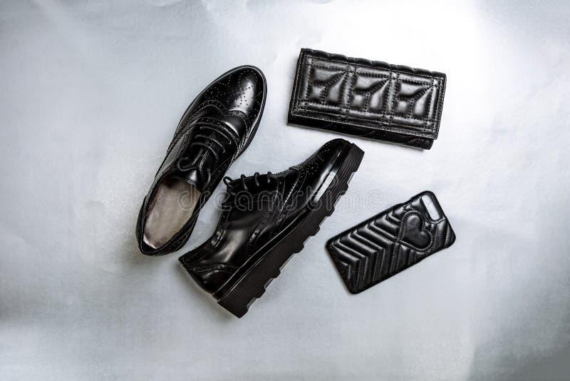 Schwarze perforierte Schuhe oxfords, ein Geldbeutel und ein Telefonkasten auf einem wei?en Papierhintergrund stockbild