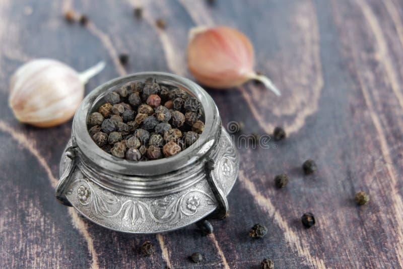 Schwarze Pfefferkörner und Knoblauchzehen auf einem Holztisch lizenzfreie stockfotografie