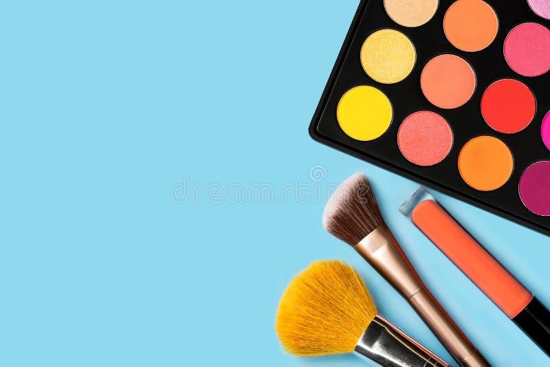 Schwarze Plastikpalette von gelber, roter hell gefärbt, rosa, orange Lidschatten, orange flüssige lipgloss und zwei Make-upbürste lizenzfreie stockfotos