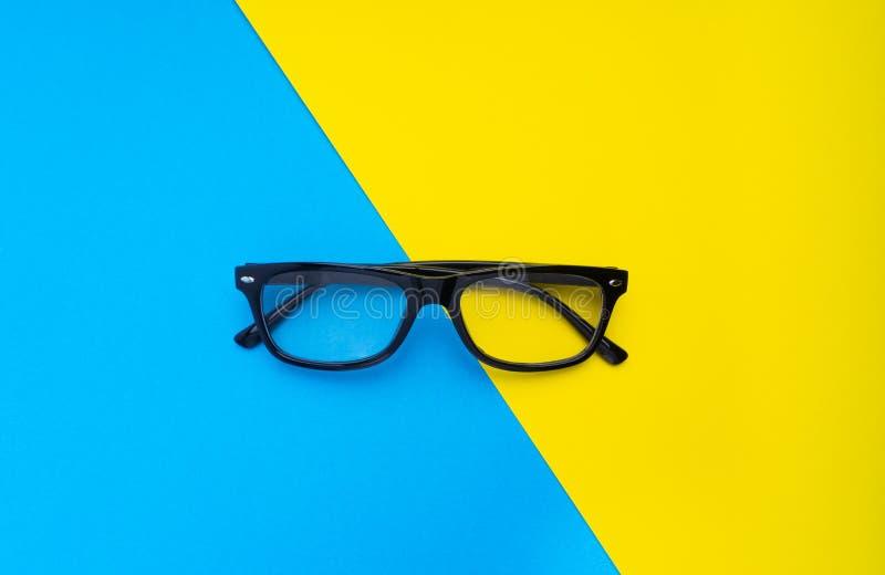 Schwarze Rahmenbrillen auf blauem und gelbem Hintergrund lizenzfreie stockfotos