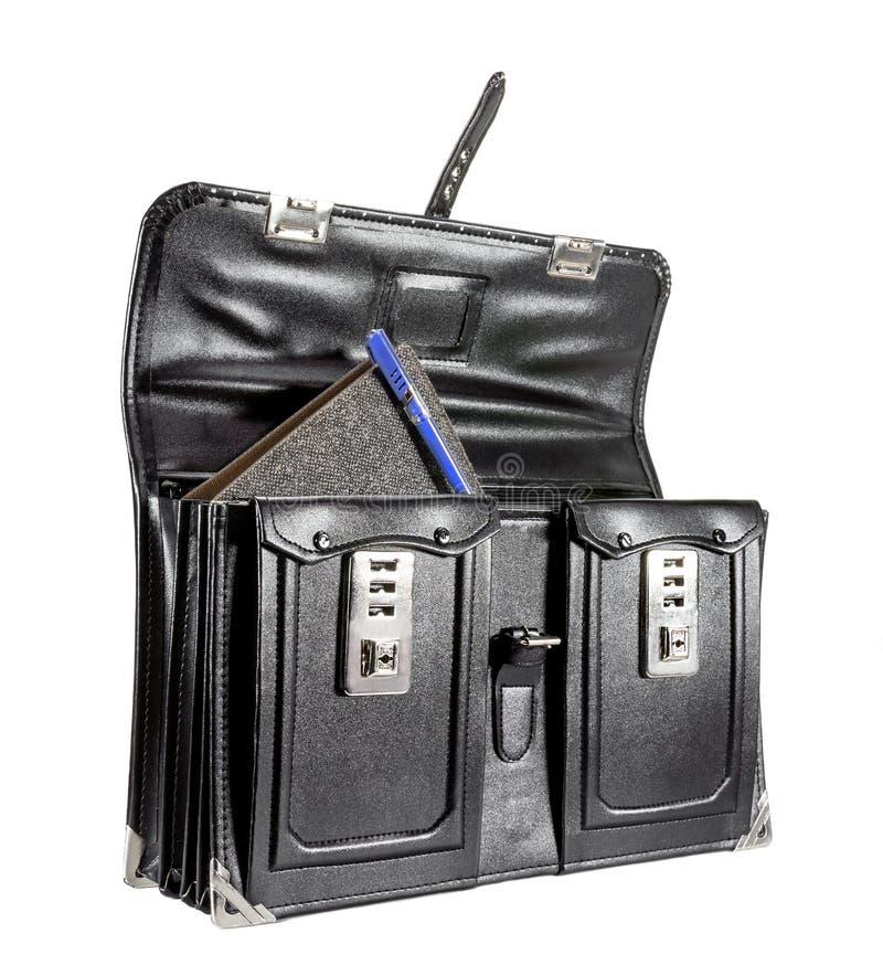 Schwarze Retro- lederne Schultasche mit Notizbuch auf Hintergrund stockbilder