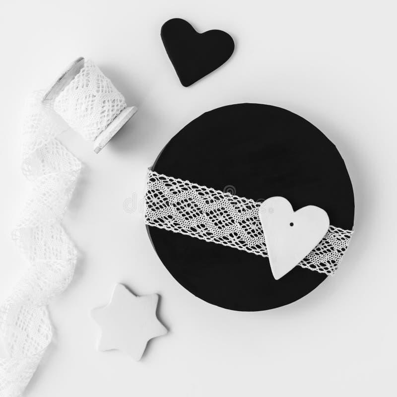 Schwarze runde Geschenkbox mit weißer Spitze auf hölzerner Rolle, handgemachte Lehmdekoration stockfoto