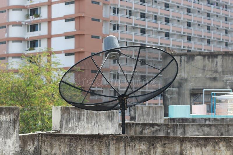Schwarze Satellitenschüssel und Fernsehantenne am alten Dorf, Parabolischer Digitalempfänger für Kommunikationsdaten bezüglich de stockfoto