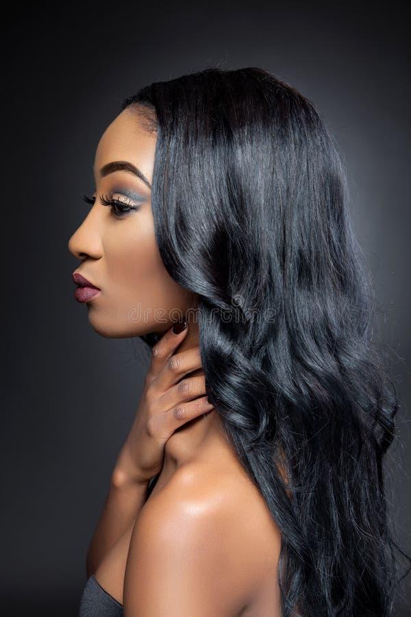 Schwarze Schönheit mit dem eleganten gelockten Haar lizenzfreies stockbild