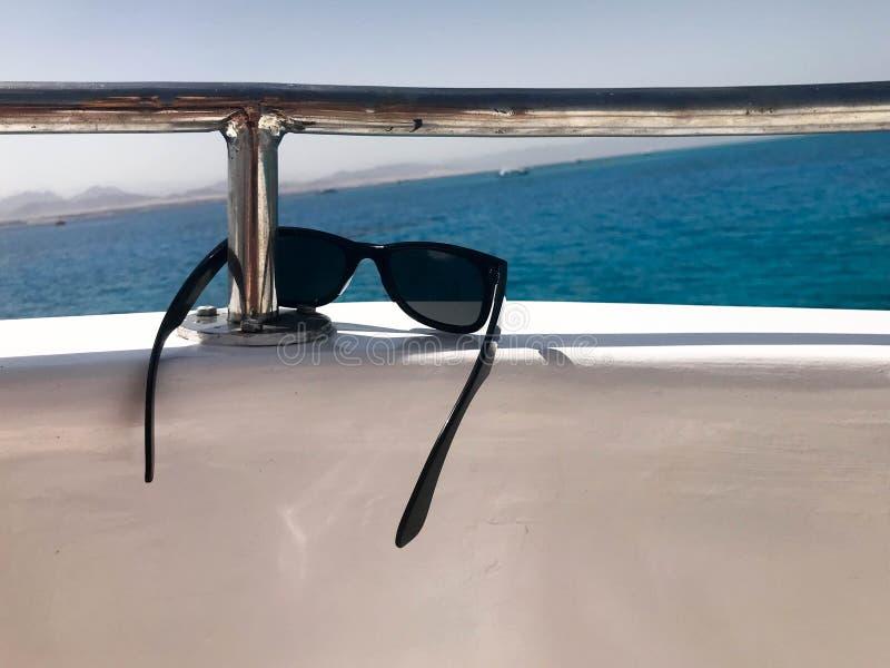 Schwarze schützende sonnen-schützende Plastikgläser hängen am Beryl an Bord eines touristischen Schiffes, einer Yacht und eines S lizenzfreies stockbild