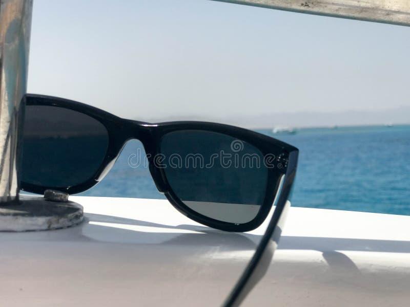 Schwarze schützende sonnen-schützende Plastikgläser hängen am Beryl an Bord eines touristischen Schiffes, einer Yacht und eines S stockbild