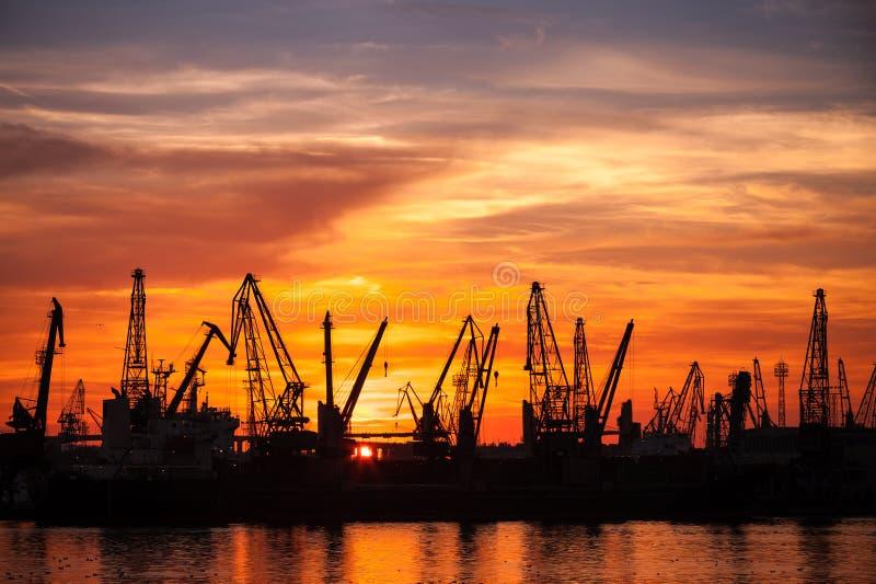 Schwarze Schattenbilder von Kränen und von Frachtschiffen im Hafen lizenzfreie stockfotografie