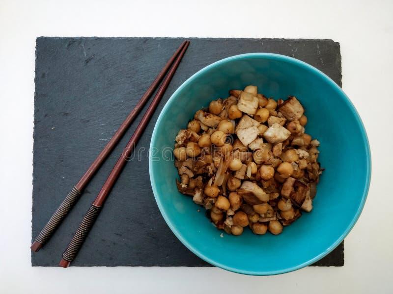 Schwarze Schieferbasis mit blauer Schüssel Kichererbsen mit Tofu und Zwiebel mit Essstäbchen auf weißem Hintergrund stockfoto