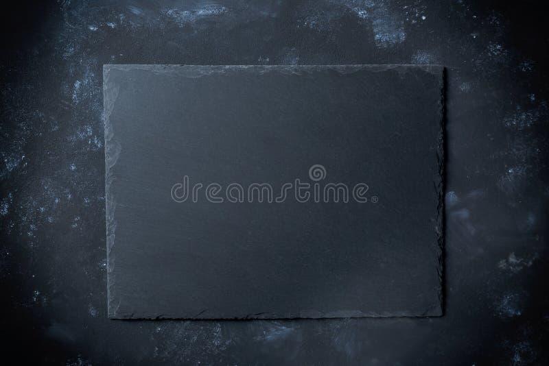Schwarze Schieferplatte auf Steinhintergrund mit Draufsicht stockfotografie
